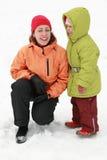 Matriz com o carrinho da filha sobre a nevar e rir foto de stock royalty free
