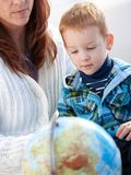 Matriz com o menino do gengibre que estuda o globo em casa Imagens de Stock
