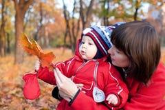 Matriz com seu filho no parque do outono Fotos de Stock Royalty Free