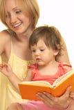 Matriz com seu livro de leitura da filha Fotos de Stock Royalty Free
