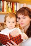 Matriz com seu livro de leitura pequeno do filho do bebê Fotografia de Stock