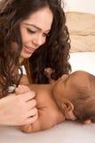 Matriz de Latina que joga com seu filho do bebé na cama Imagem de Stock