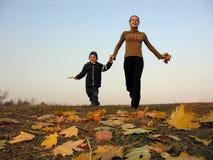 Matriz de passeio com o filho nas folhas de outono Imagem de Stock Royalty Free