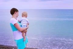 Matriz e bebê que jogam na praia Olhe o mar Fotos de Stock Royalty Free