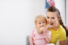 Matriz e bebê que mordem o bolinho do coelho de Easter fotos de stock royalty free