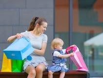 Matriz e bebê que olham no saco de compra Foto de Stock Royalty Free