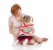A matriz e a criança felizes leram um livro junto Fotografia de Stock Royalty Free