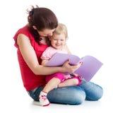 A matriz e a criança felizes leram um livro junto Imagens de Stock