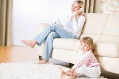 A matriz e a criança na sala de visitas prestam atenção à televisão Imagens de Stock Royalty Free