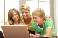 Matriz e crianças adolescentes que usam o portátil em casa Imagem de Stock