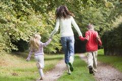 Matriz e crianças que funcionam ao longo do trajeto da floresta Imagens de Stock Royalty Free