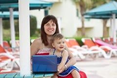 Matriz e filha felizes com portátil Imagens de Stock