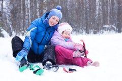 A matriz e a filha felizes em um inverno estacionam Foto de Stock