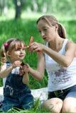 Matriz e filha nas calças de brim com brinquedo Imagem de Stock Royalty Free