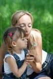 Matriz e filha nas calças de brim com dente-de-leão Fotografia de Stock Royalty Free
