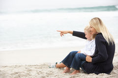 Matriz e filha no feriado que senta-se na praia Fotos de Stock Royalty Free