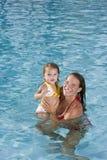 Matriz e filha nova que apreciam a piscina Fotografia de Stock Royalty Free
