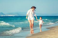 Matriz e filha que andam na praia Imagens de Stock Royalty Free