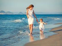 Matriz e filha que andam na praia Fotos de Stock