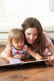 Matriz e filha que aprendem ler em casa Fotos de Stock Royalty Free