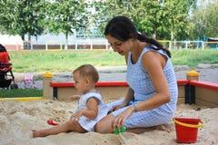Matriz e filha que jogam em uma caixa de areia imagens de stock