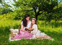 Matriz e filha que lêem um livro Fotografia de Stock
