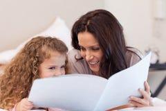Matriz e filha que lêem um livro junto Foto de Stock Royalty Free
