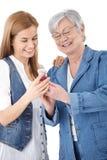 Matriz e filha que olham fotos no móbil Fotos de Stock