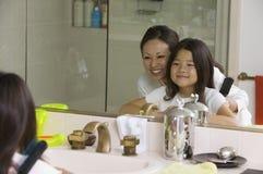 Matriz e filha que olham o espelho da reflexão imagens de stock