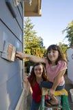 Matriz e filha que pintam uma casa - vertical Fotografia de Stock