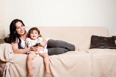 Matriz e filha que prestam atenção à tevê Imagens de Stock