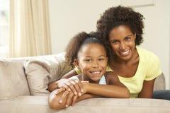 Matriz e filha que relaxam no sofá em casa foto de stock