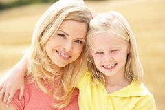 Matriz e filha que sentam-se em balas da palha em Harv Fotos de Stock Royalty Free
