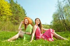 Matriz e filha que sentam-se na grama verde Imagem de Stock Royalty Free