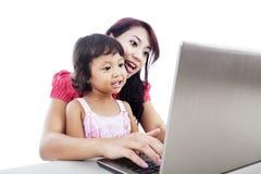 Matriz e filha que usa o portátil Fotos de Stock