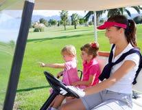 Matriz e filhas da família do campo de golfe no buggy imagem de stock