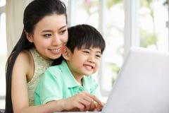 Matriz e filho chineses que usa o portátil em casa Imagens de Stock