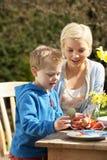 Matriz e filho que decoram ovos de Easter Foto de Stock