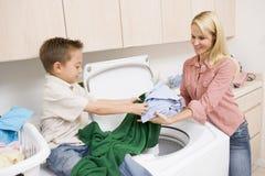 Matriz e filho que fazem a lavanderia Fotos de Stock Royalty Free