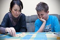 Matriz e filho que jogam dados Imagens de Stock