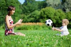 Matriz e filho que jogam a esfera no parque. foto de stock