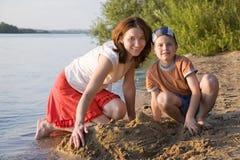 Matriz e filho que jogam na areia Fotos de Stock Royalty Free