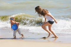 Matriz e filho que jogam na praia imagens de stock