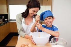Matriz e filho que têm o divertimento preparar um bolo Imagem de Stock