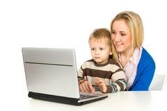 Matriz e filho que usa o portátil Fotografia de Stock Royalty Free