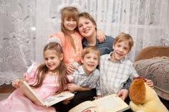 Matriz e livro de leitura felizes de quatro crianças. Foto de Stock Royalty Free