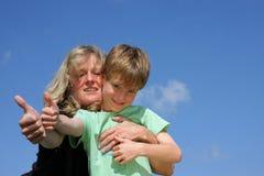 A matriz e o filho que levantam com os polegares levantam o sinal Fotos de Stock Royalty Free