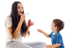 A matriz e o filho têm o divertimento com bolha de sabão junto Foto de Stock