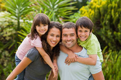 Matriz e pai que dão a crianças um sobreposto foto de stock