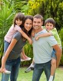 Matriz e pai que dão a crianças um sobreposto Imagem de Stock Royalty Free